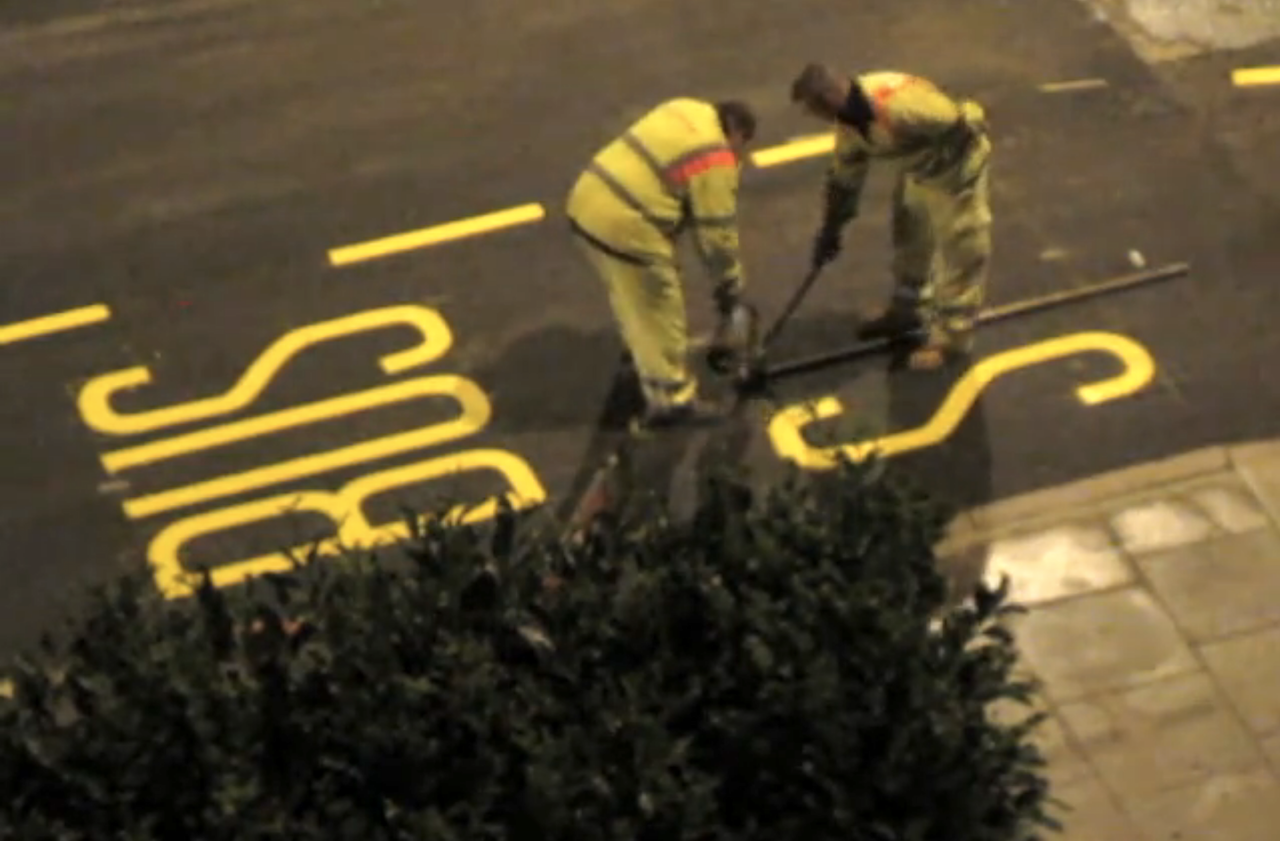 A Timelapse of Two Street Workers Expertly Painting the Letters For a 'Bus Stop' on a London Road