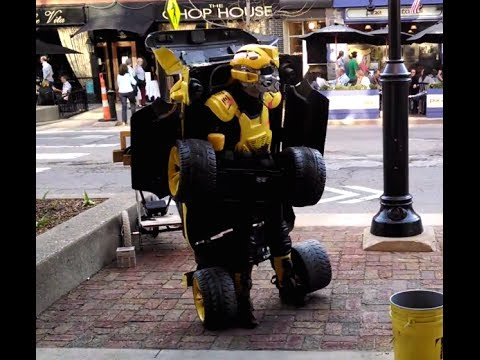 Transformer Street Performer Entertains Kids by Converting From a Robot Into a Yellow SUV That Drives Around