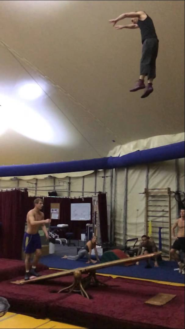 Two Acrobats Use a Teeterboard to Catapult Each Other in the Air and Perform Back Flips