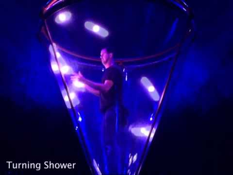 Man Juggles Nine Glowing Balls in Various Patterns Inside a Transparent Cone