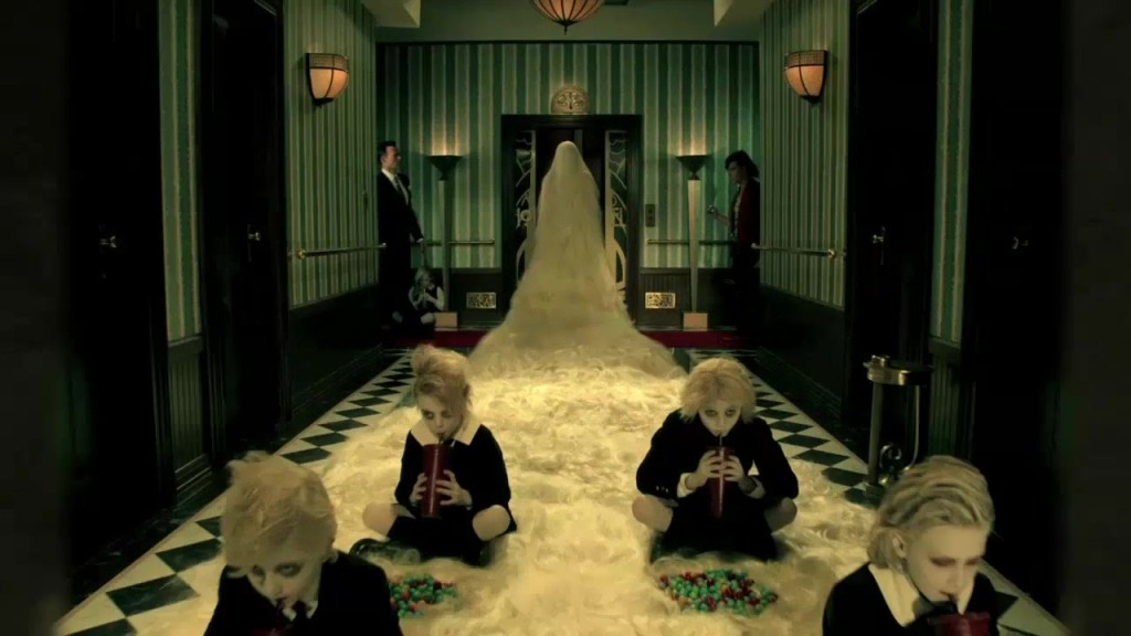 A Towheaded Child Runs Down a Busy Hallway of Eccentric Characters in the Promo for 'American Horror Story: Hotel'