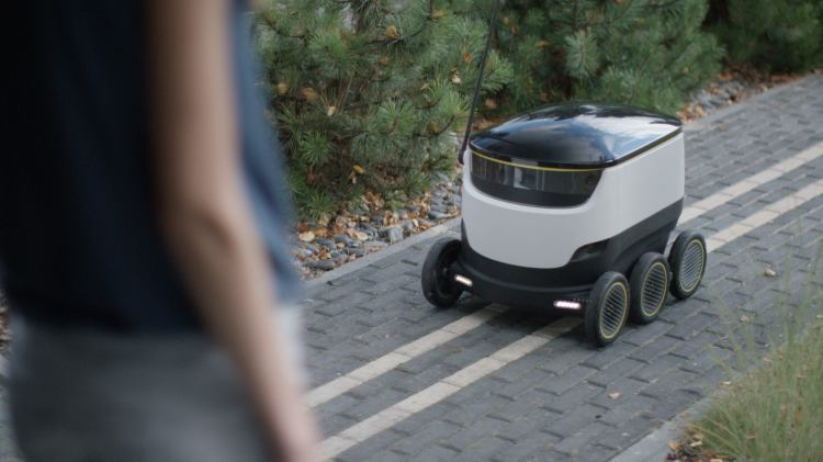 Starship Technologies Delivery Robot Rolling on a Walkway
