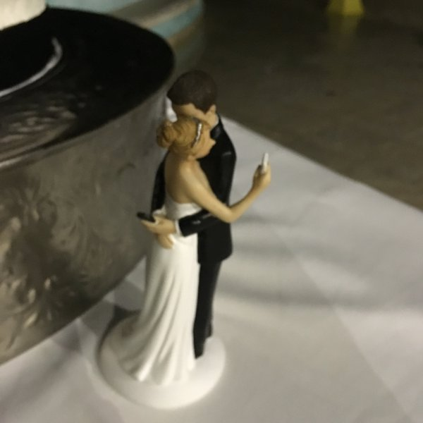 Wedding Cake Topper Featuring a Bride and Groom Checking Their