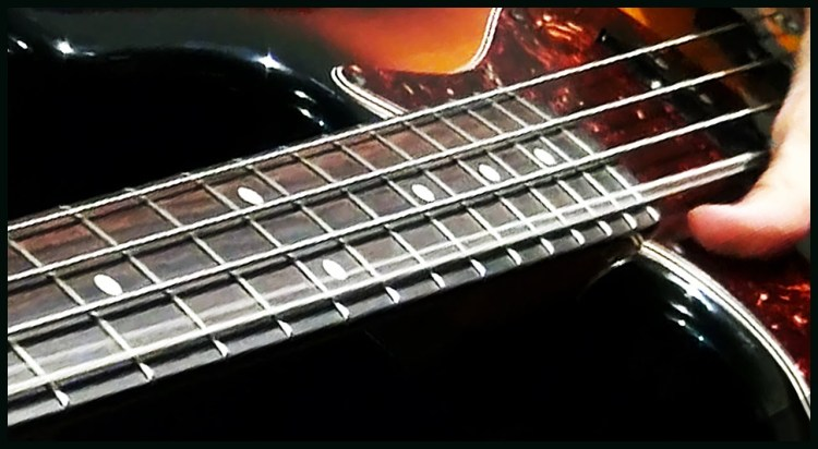 Musician Performs Left Handed on a Bass With Inverted Strings That Go From High to Low
