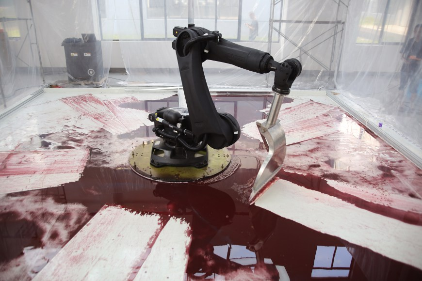 A Large Robotic Arm Futilely Tries to Clean a Blood Red Mess in the