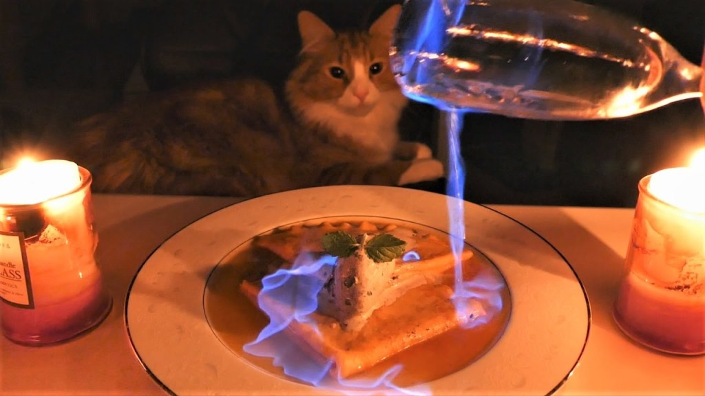 Talented Cook Prepares a Fiery Recipe of Crepes Suzette Under the Watchful Eyes of His Two Cats