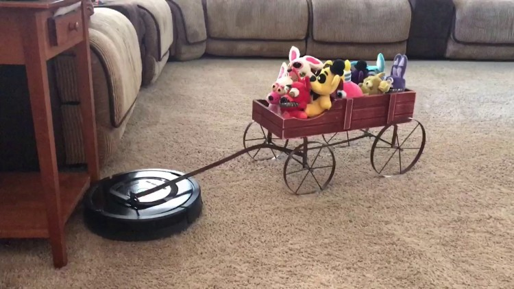 A Thoughtful Roomba Pulls a Wagon Full of Plush Toys For a Short Ride Around the Living Room