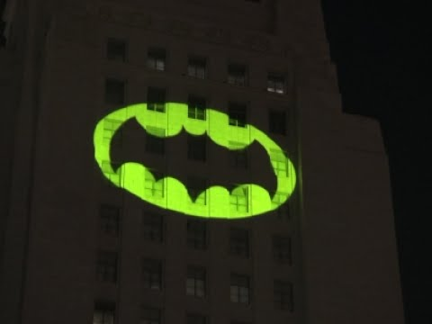 Adoring Crowd Watches the Iconic Bat Signal Light Up Los Angeles City Hall In Memory of Adam West