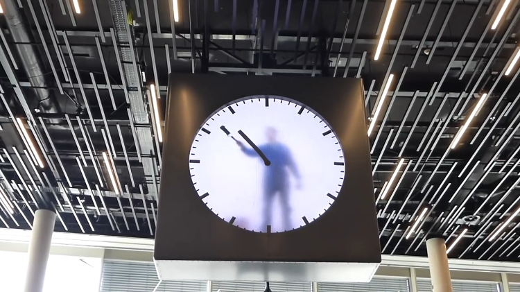 A Man Paints the Time From Within a Clock In a Clever Video Installation at the Amsterdam Airport