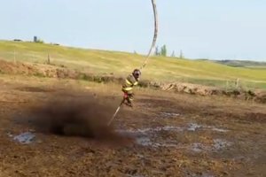 A Daring Firefighter Holds on Tight to a Powerful Fire Hose While Being Whipped Around a Mud Pit2