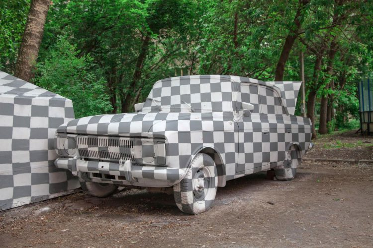 Street Artists Visually Delete an Abandoned Car With a Photoshop Transparency Checkerboard Pattern