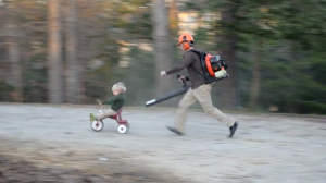 Father Uses a Lead Blower to Push His Little Son on a Tricycle