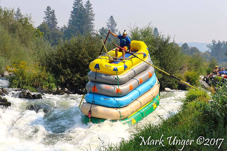 Daring Man Goes Down a River With Class 4 Rapids On Top of 6 Rafts That Are Strapped Together