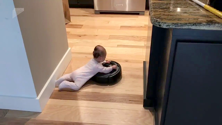 Cute Baby Hangs Onto a Roomba to Take a Ride Around the Kitchen