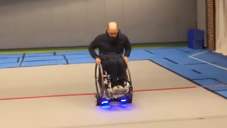A Man Rides Around on a Wheelchair That Is Mounted On Top of a Hoverboard