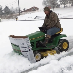 Creative Man Plows Snow Covered Driveway With Riding Lawnmower and a Large Cardboard TV Box