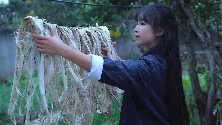 A Woman Gracefully Demonstrates the Traditional Chinese Art of Making Paper by Hand