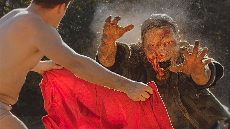 A Half Naked Matador Battles a Zombie to Prove His Worth at a Survivor Camp