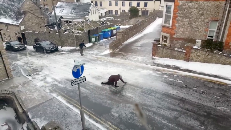 A Group of People Unsuccessfully Try to Walk and Crawl Up an Icy Hill in Swanage, England