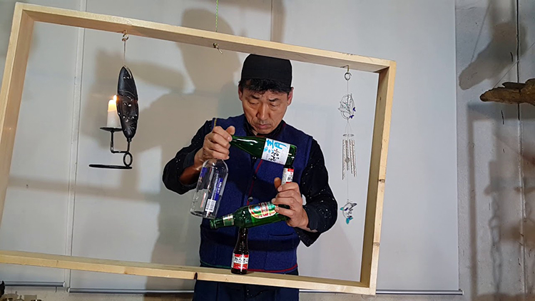 Balancing Expert Stacks Bottles to Form the Shape of a Square Inside of a Wobbly Wooden Frame