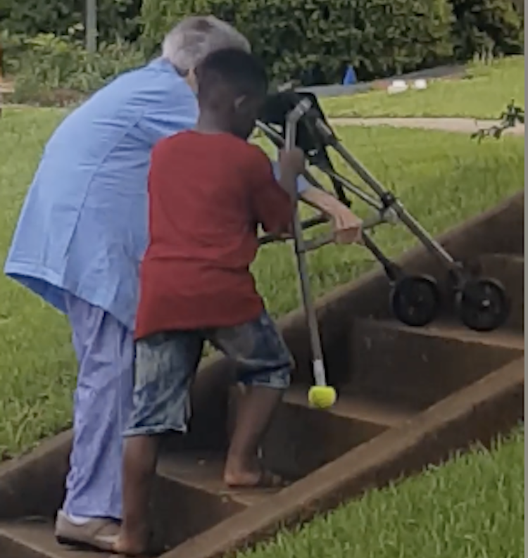 Boy Helps Elderly Woman Up Stairs