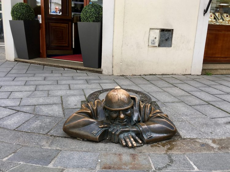 Amusing Brass Statue of Man in a Hard Hat Poking His Head Out of a Sewer in Bratislava, Slovakia