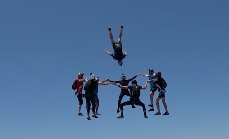 Daring Skydivers Take Turns Flying Through a Human Ring Formed in Mid-Air by Other Daring Skydivers
