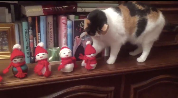 A Scroogelike Calico Cat Deliberately Knocks a Family of Handmade Christmas Figurines Off the Mantle