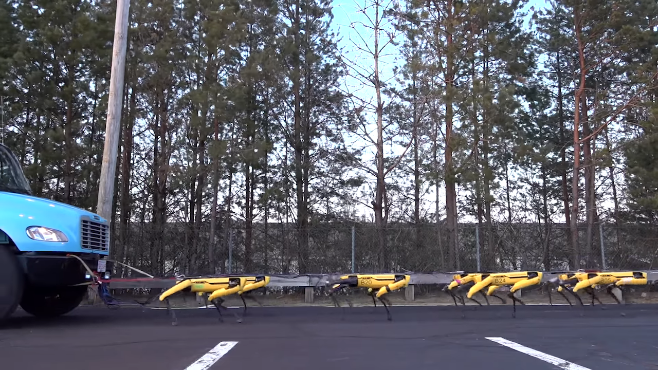 A Harnessed Herd of Ten Four-Legged SpotMini Robots Pull a Truck Across the Boston Dynamics Parking Lot