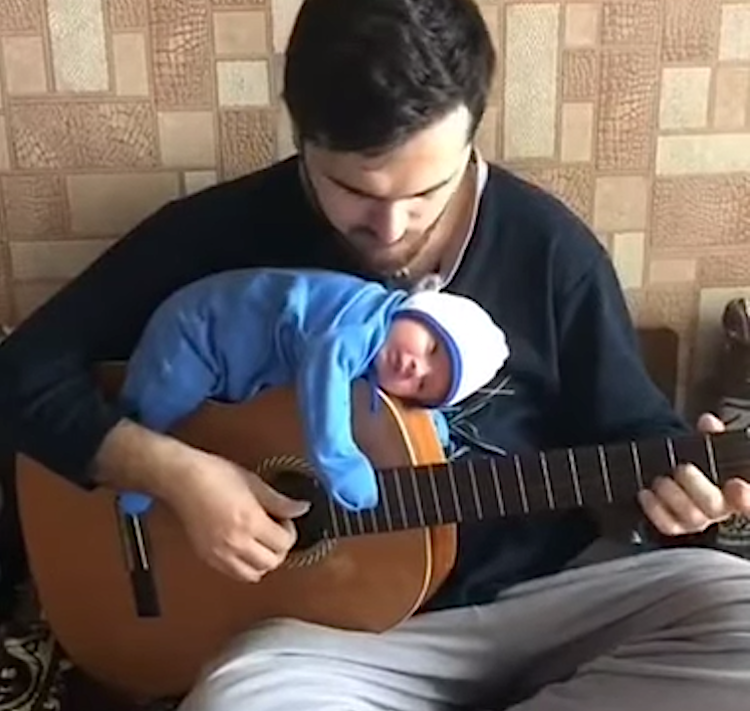 Musician Dad Plays a Jaunty Jazz Tune While His Tiny Baby is Lulled to Sleep on Top of His Guitar