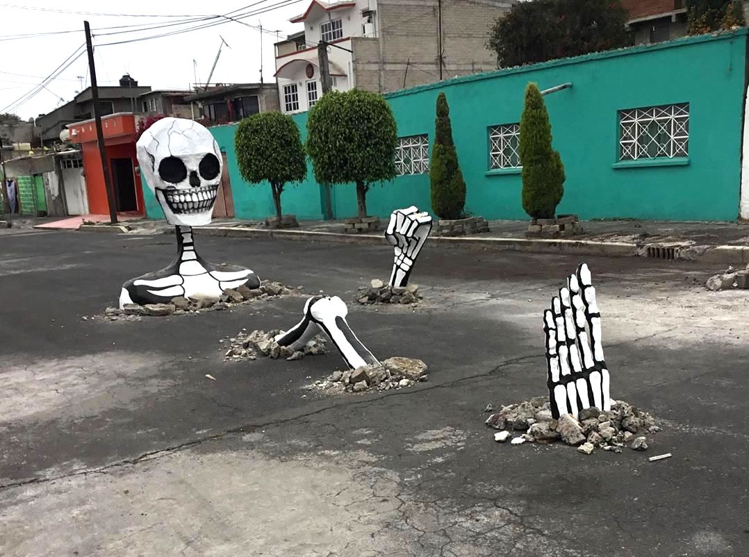 A Giant Skeleton Emerges From the Pavement of a Street in Mexico City During Día de Muertos