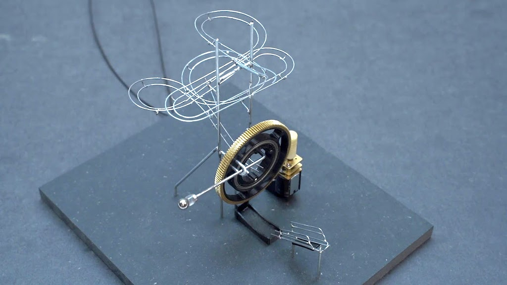 A Marvelous Mini Marble Machine That Automatically Sends a Magnetic Ball Over a Curving Steel Wire Track - laughing squid